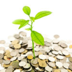 Green seedling growing out of a pile of coins.